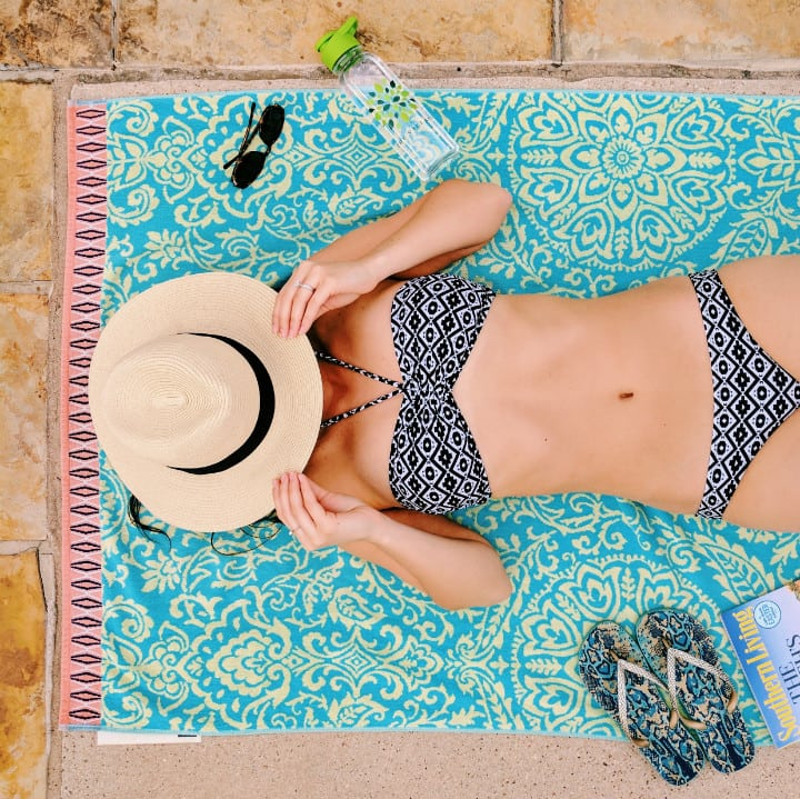 Bikini body guide. Girl in bikini on towel with hat.