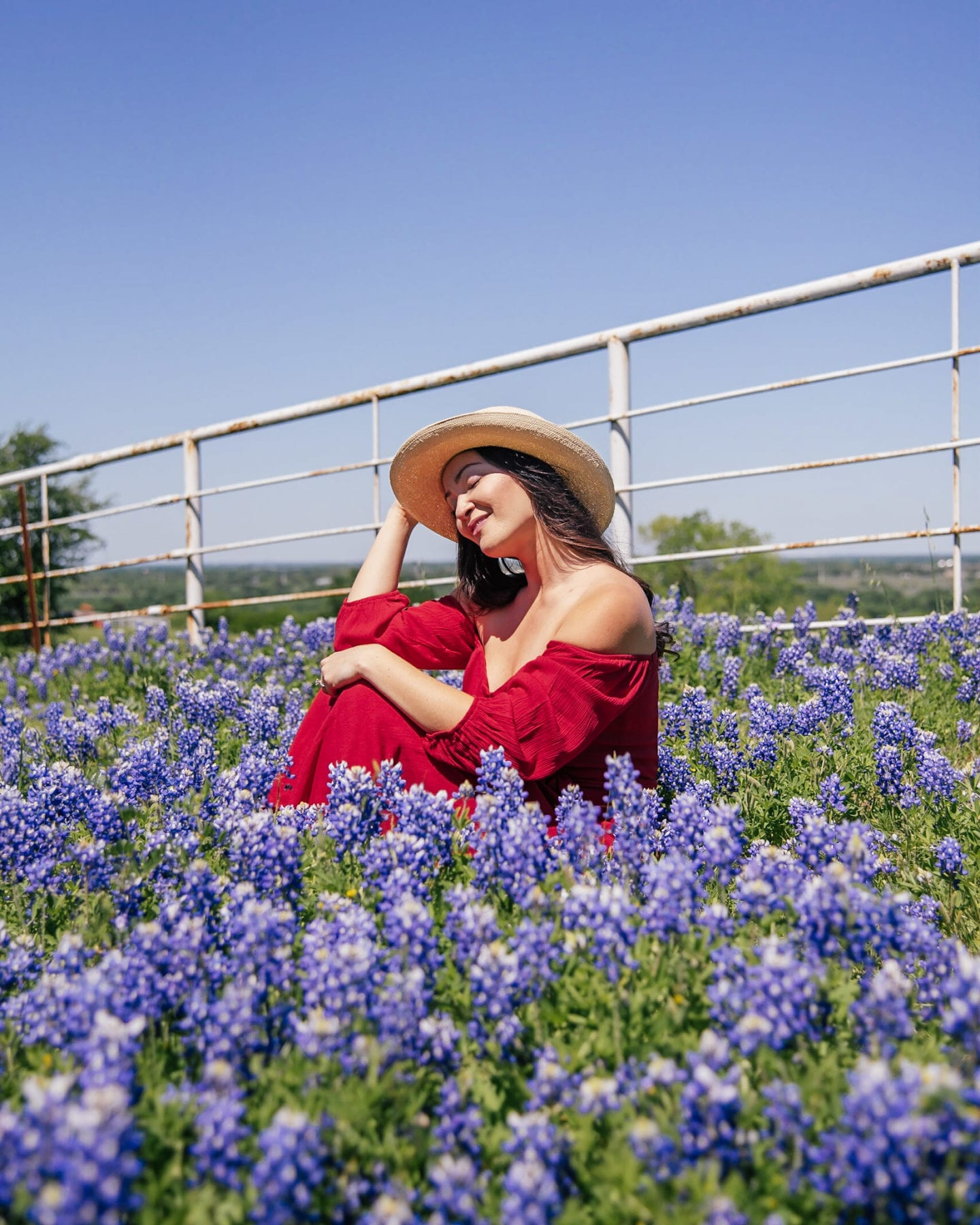 girl sitting in bluebonnets