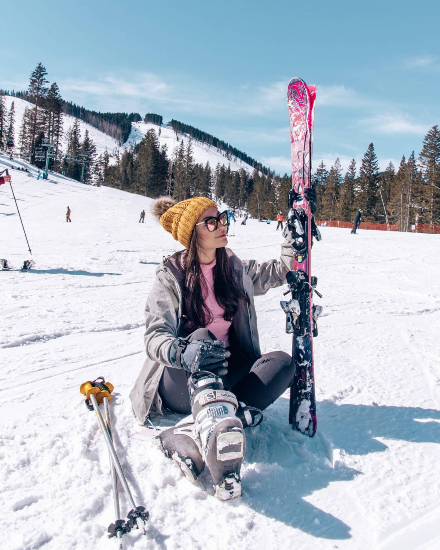 girl sitting on snow holding skis