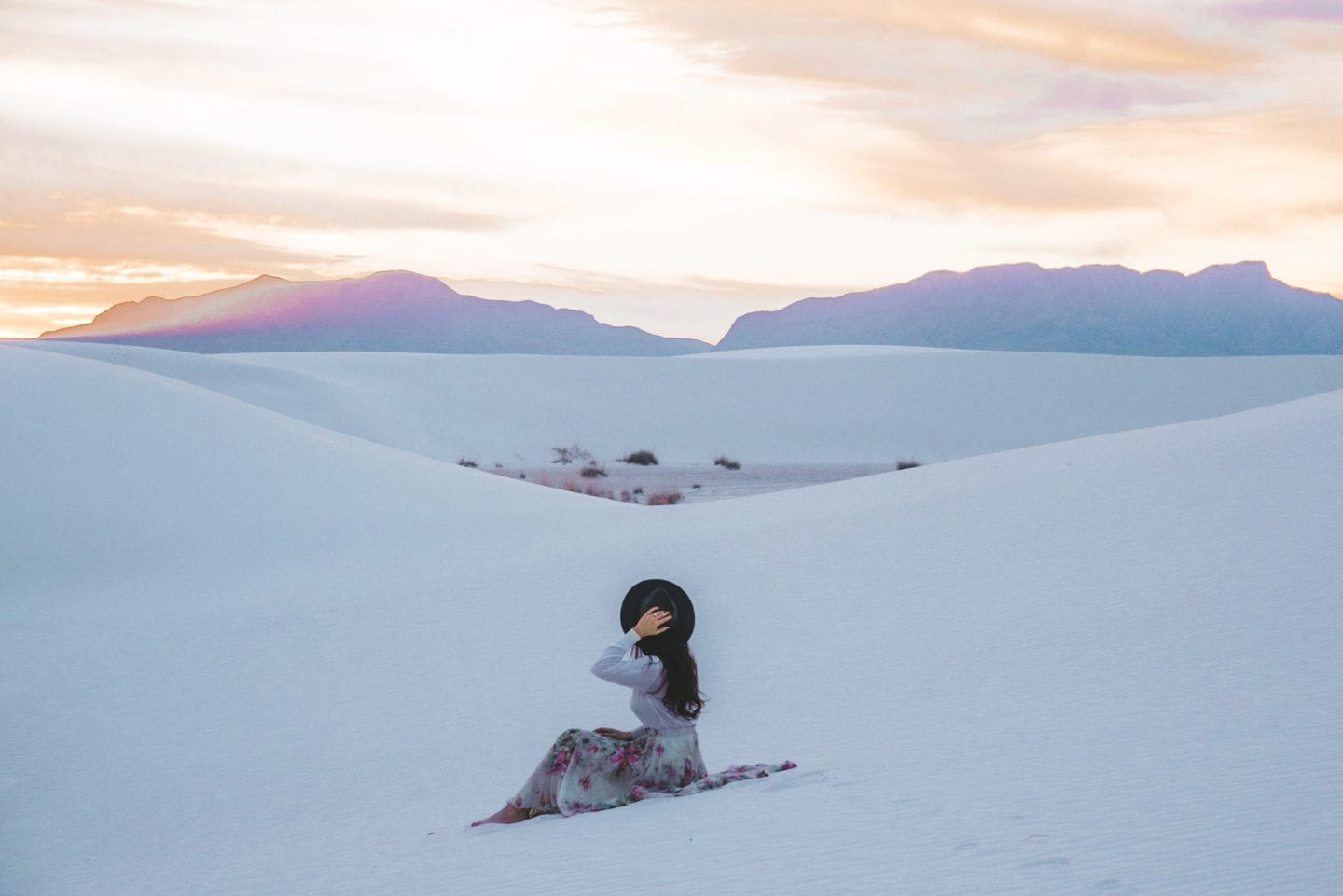 girl sitting on sand at white sands national monument