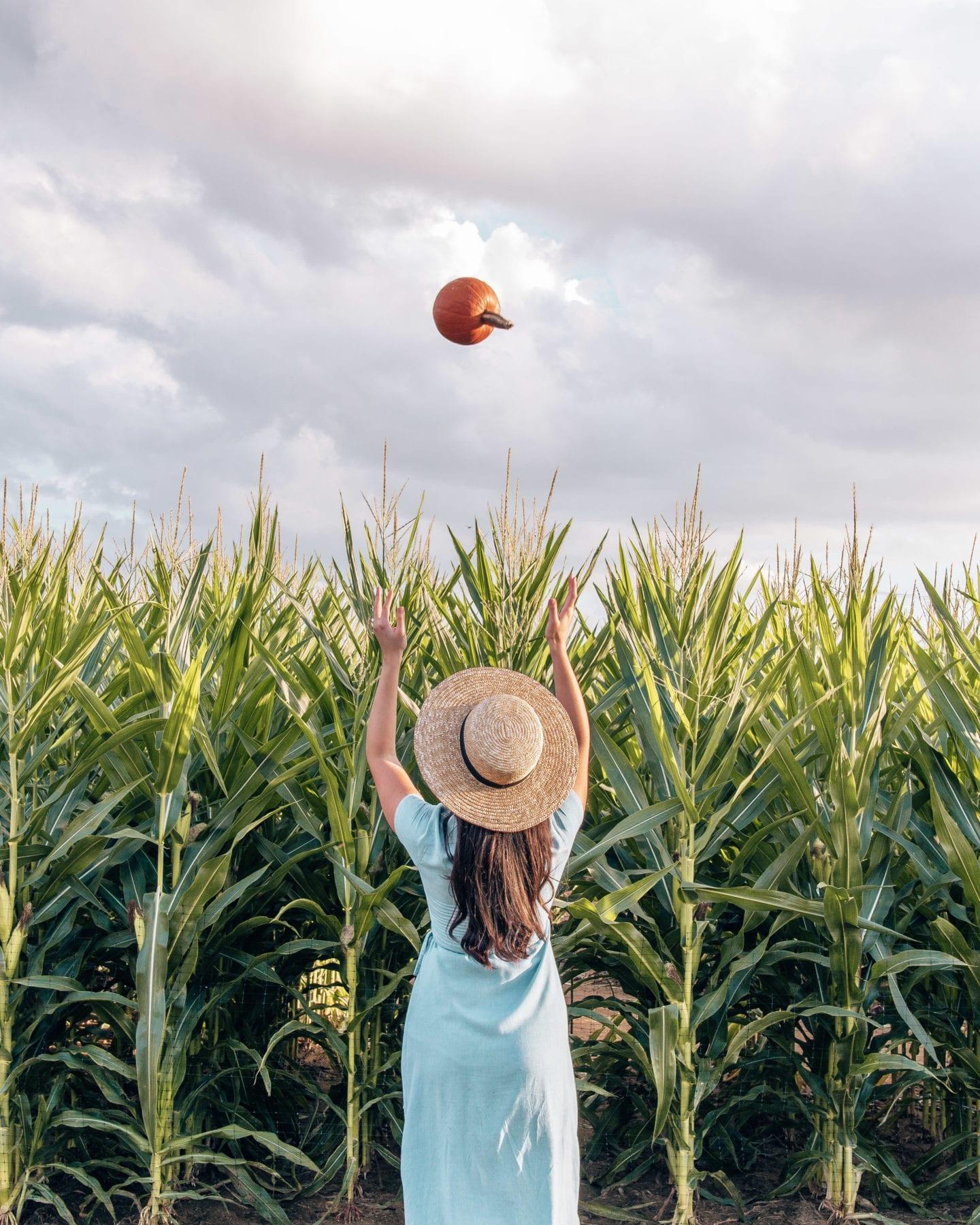 girl throwing pumpkin up into air