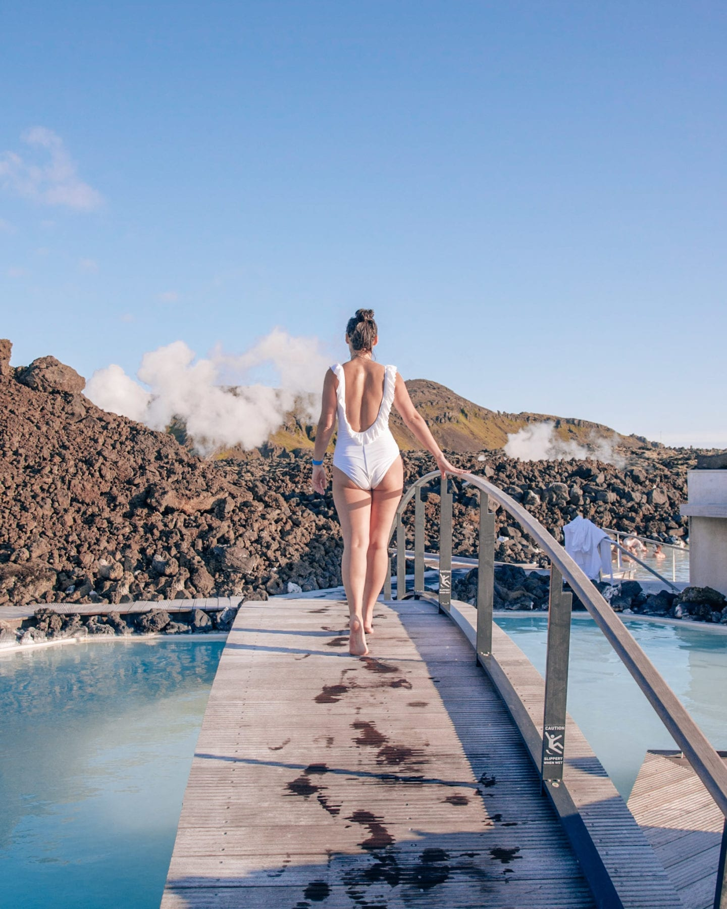 girl walking on bridge at blue lagoon iceland