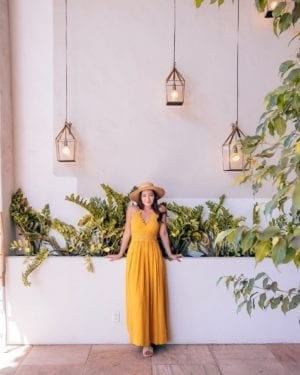 girl in front of white wall with plants and lights