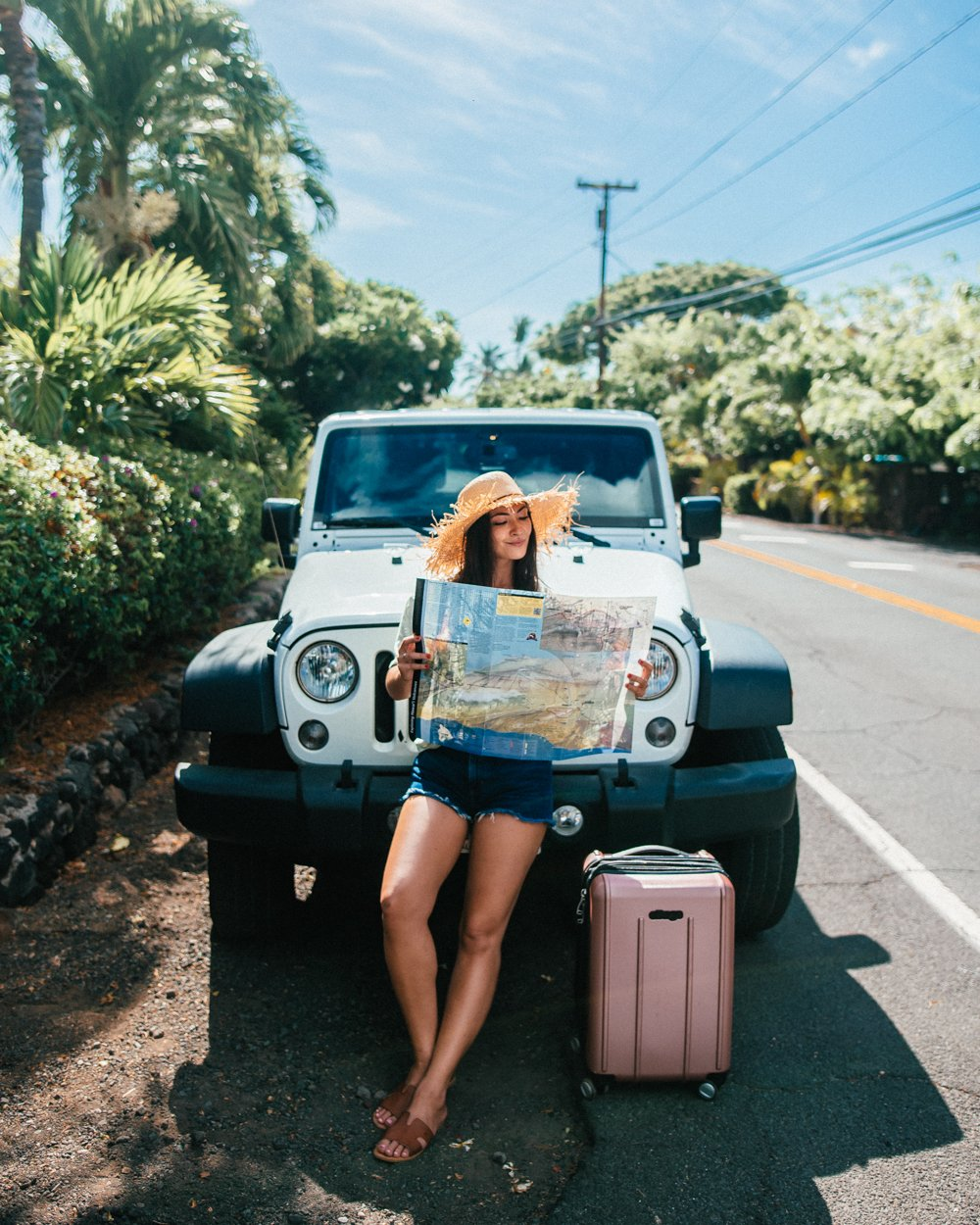 girl reading map jeep suitcase hawaii